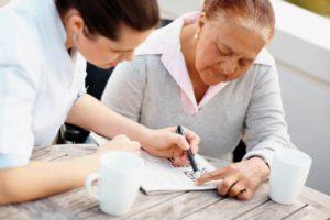 Caregiver providing respite care to senior woman doing crossword | Cost of Care at Neighborly Home Care