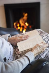 senior-woman-reading-book by the fire - elderly care winter tips - Neighborly Home Care