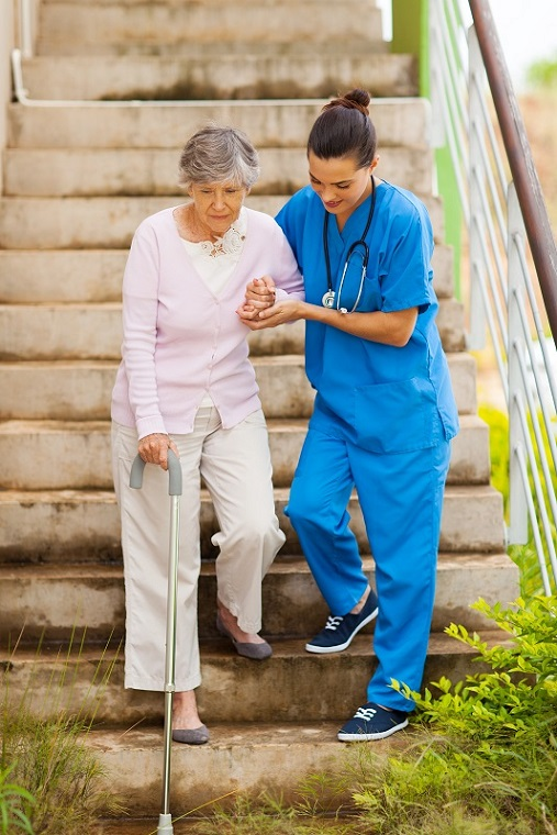 senior home care nurse helping elderly woman walk down stairs