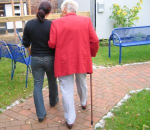Woman walking with senior woman who is using a cane   Keep Seniors Active   Neighborly Home Care