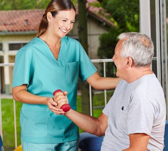 Nurse helping elderly man with weights | Intergenerational housing | Neighborly Home Care