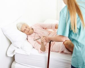 nurse helping elderly woman out of bed