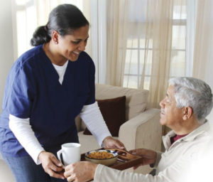 Caregiver helping senior man with meal | facts about senior care services | Neighborly Home Care