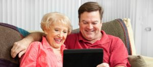 Adult son and elderly mother looking at a tablet together | Telemedicine Can Help Seniors | Neighborly Home Care