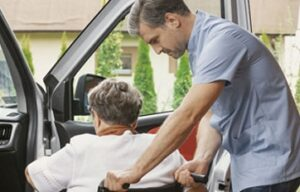 caregiver assisting senior woman from wheelchair into car | senior transportation services help alleviate one of the challenges seniors face living at home alone | Neighborly Home Care