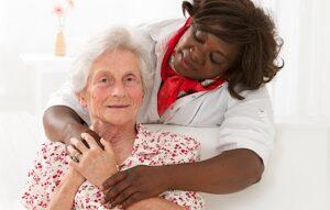 Senior woman with caregiver hugging | exploring dementia | Neighborly Home Care